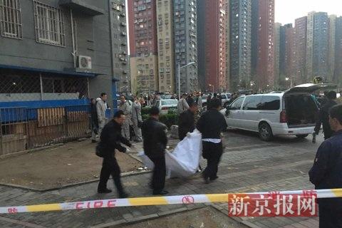 18时50分许,一具尸身被裹在红色裹尸袋内抬出。新京报记者 林野 摄