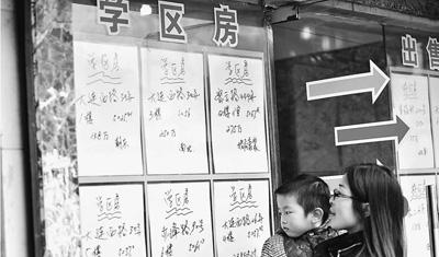 """图为上海一名家长带着孩儿在中介门口看""""学区房""""房源。"""