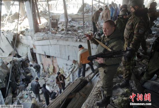 资料图:当地时间2015年2月25日,顿涅茨克,乌克兰战俘在亲俄民间武装控制的机场大楼废墟里搜寻和挖掘同伴的遗体。