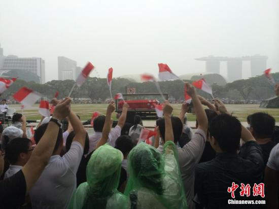 3月29日,新加坡建国总理李光耀的国葬仪式举行,移灵队从国会大厦出发,前往新加坡国立大学文化中心,沿途成千上万民众在倾盆大雨中送别。中新社发 李洋 摄