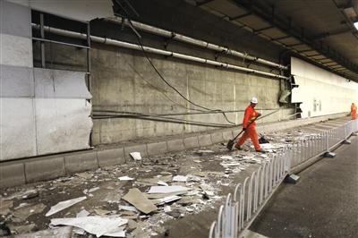 大屯路隧道内,北侧约70平米墙皮被剐蹭掉,救援人员正在清理。新京报记者 浦峰 摄