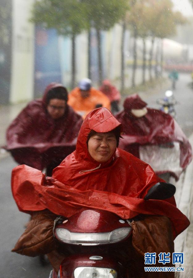 4月12日,人们在风雨中艰难出行。当日下午,江苏扬州遭遇大风暴雨天气,气温骤降,恶劣天气持续近一个小时,给市民出行带来不便。 新华社发(孟德龙)