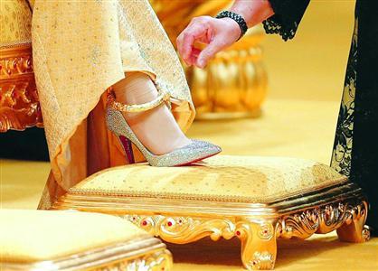 新娘脚穿镶满水晶的高跟鞋,戴着纯黄金脚链。