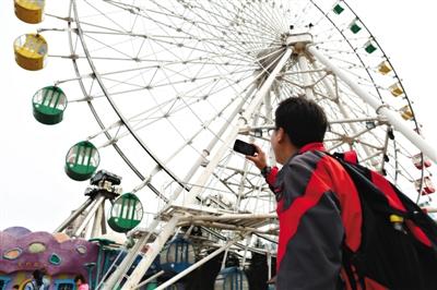 """昨天,石景山游乐土,一旅客在给乘坐摩天轮的妻儿拍视频。这座29岁的摩天轮将于月尾""""服役""""。新京报记者 浦峰 摄"""