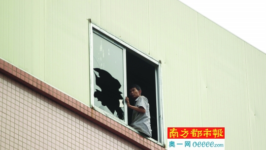 昨日上午,高新东路。讨薪工人打碎了玻璃窗,坐在工厂四楼的窗台上。南都记者 孙振飞 摄