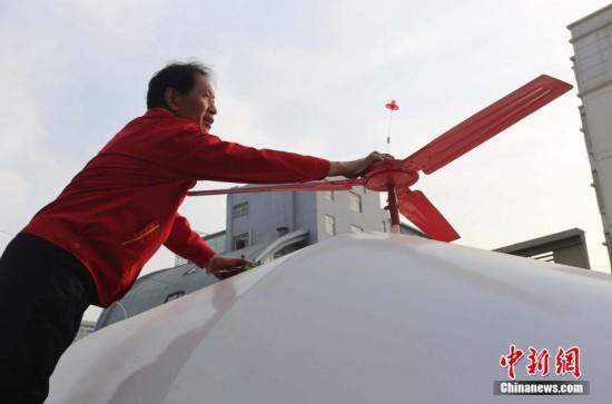 """4月21日,在郑州市商都路上,袁精英在擦洗他制作的""""直升机""""。"""