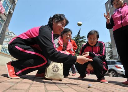 近百名老年居民在此玩起孩童时代的老游戏:打纸牌,拾波谷,跳房子,弹