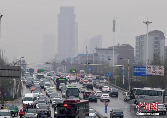 """4月1日,河北石家庄一主干路车流缓慢""""蠕动""""。冷空气""""入侵""""中国中东部多地,伴随降雨,河北省大部分地方气温持续降低,1日至2日,该省会再次出现降水天气,南部、东部的部分地区降中雨,局部大雨,张家口、承德、保定西北部气温较低有小到中雨夹雪。雨雪天气路面湿滑,能见度变差,给市民出行造成一定影响。 中新社发 翟羽佳 摄"""