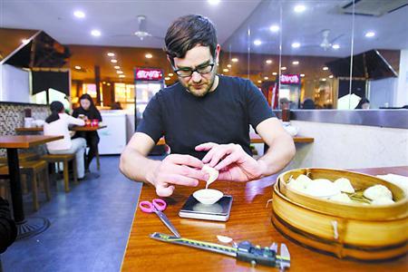 对着一笼热腾腾的汤包,Chris用一台准确到0.01克的电子秤称汤包碟子的分量。蒋迪雯 摄