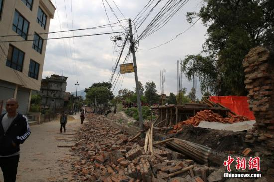据中国地震台网正式测定:4月25日14时11分在尼泊尔(北纬28.2度,东经84.7度)发生8.1级地震,震源深度20千米。尼泊尔首都加德满都震感强烈。记者目睹一堵墙被震塌,周围大批居民奔跑到空旷地带,狗叫声四起,手机信号中断。图为加德满都部分房屋倒塌。中新社发 符永康 摄