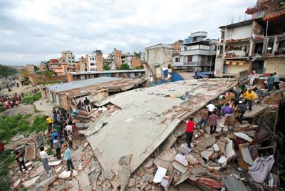加德满都,民众聚集在坍塌的房屋旁边。