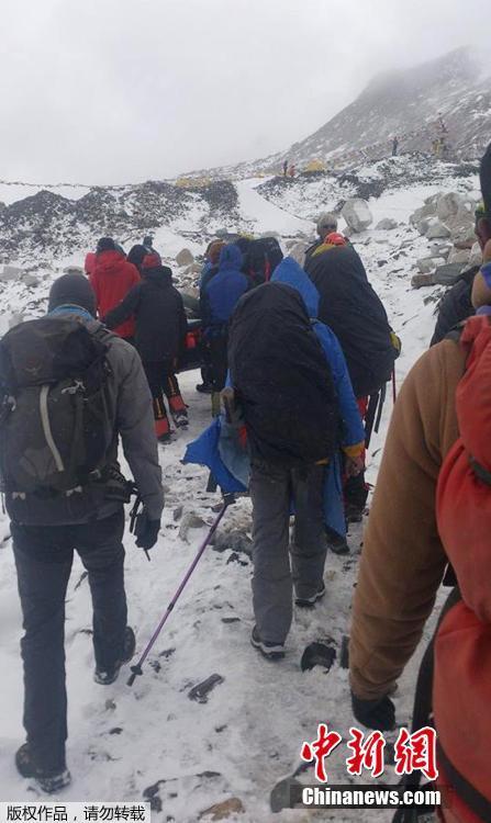 当地时间2015年4月25日,登山者和向导抬着在珠峰雪崩中受伤的人员撤离。