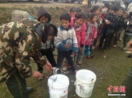 4月26日,西藏日喀则边防支队吉隆边防大队曲松多边境检查站官兵转移群众至安全地带,并为他们送上御寒衣物,提供早餐。 西藏边防总队供图 视频:尼泊尔地震:西藏吉隆县和聂拉木县正在救援 来源:央视新闻