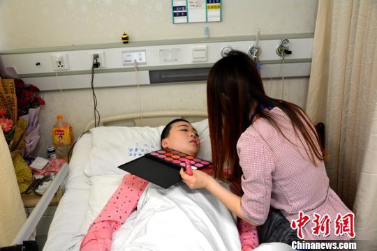 图为:作业人员正在给董慧在病床上化装。 刘彦君 摄