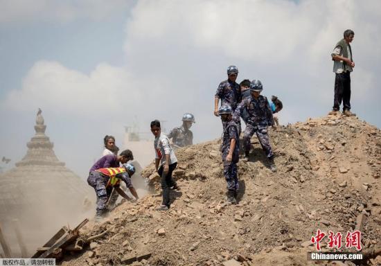 当地时间2015年4月27日,尼泊尔加德满都,尼泊尔警察在一处坍塌的庙宇徒手清理瓦砾,寻找幸存者。 视频:尼泊尔震中廓尔喀画面公布 一片狼藉来源:央视新闻
