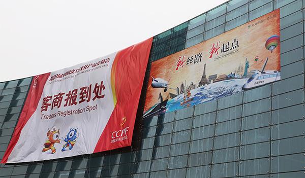 """图:文交会举办地义乌国际博览中心外墙上悬挂的宣传广告,上面写着""""图片"""