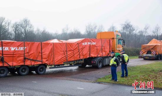 资料图:当地时间2014年12月9日,运送马航MH17航班残骸的卡车车队定于抵达荷兰南部的希尔泽.赖恩空军基地。空难调查人员将利用残骸再次拼装这架客机,以期找出失事原因。