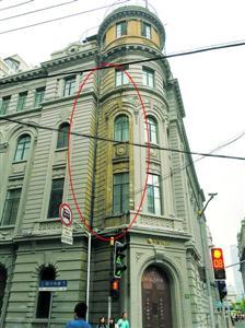 """懿德大楼违规翻新未竣工被叫停,大楼外墙出现出""""阴阳脸""""(红圈内为还没有被喷涂局部)。舒抒摄"""