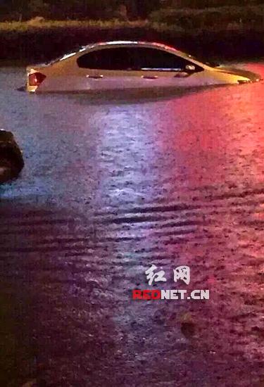 (长沙韶山南路上,不少小车被淹在路面积水中。)