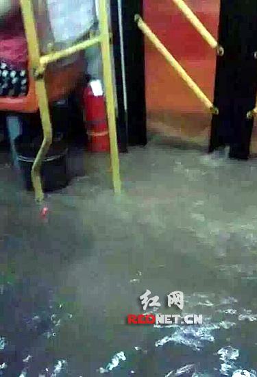 (暴雨导致路面积水淹进了公交车车厢里。)