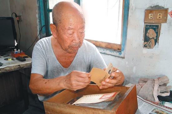 百岁抗战老兵王从志看着他珍藏的当兵资料,他独居的住处简陋斑驳。 图自台湾《联合报》