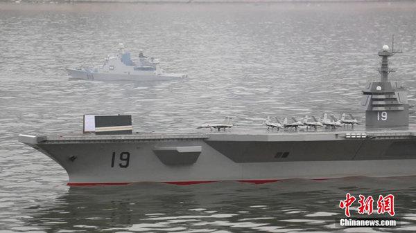 """原文配图:图为5月6日,河南周口沙颍河上演一场""""航母海战"""",号称国内最大的一艘航母模型""""河南号""""带领4艘驱逐舰参与""""海战""""演习。杨正华 摄"""
