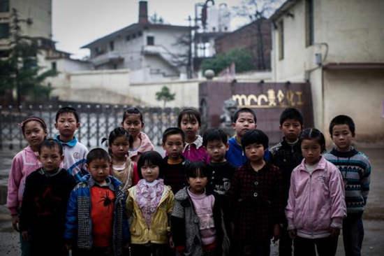 2014年4月24日,湖南省衡东大浦镇,局部得了血铅症状的孩儿站在本地美仑化工场前。