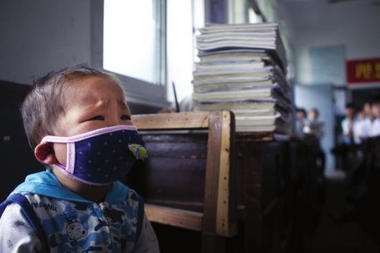 图图一个人坐在教室门边的椅子上,因为有些不舒服,他老是皱着眉头轻声哭泣。 组图/潇湘晨报记者陈正