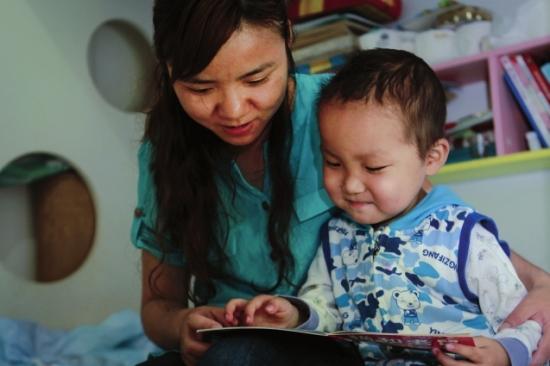 做完家务活,张薇带着图图看漫画书,母子俩沉浸在故事中。组图/潇湘晨报记者陈正