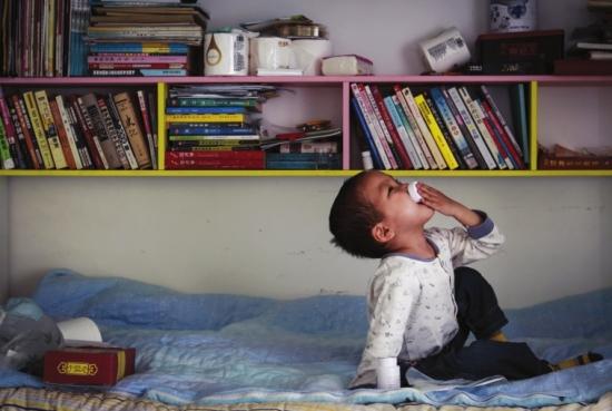 出租屋内,图图坐在床上自己吃药。 组图/潇湘晨报记者陈正