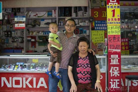 ● 找回母亲的刘立胜抱着儿子和母亲欧菊元在本人的档口合影。