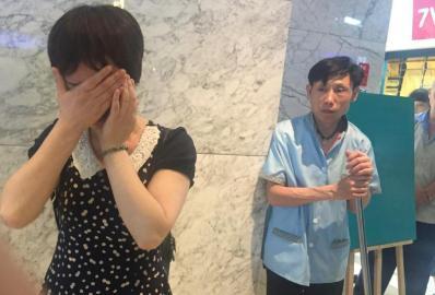 成都市中心一商场外,吴女士向记者讲述她被负责人查包的做法感到委屈。