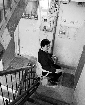 吴姨妈在用新装好的座椅式电梯下楼。