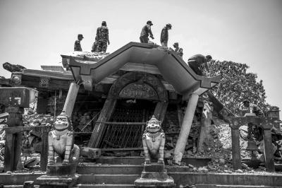 5月12日,人们在尼泊尔古城帕坦清理被破坏的景点。新华社发