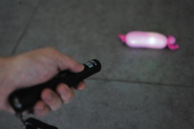 克日,记者检测用激光笔能否能打爆气球。当气球吹得半满时,激光笔照耀5分钟并无将其打爆。但将气球吹到最大,翻开激光笔时气球霎时被打爆。新京报记者 薛珺 摄