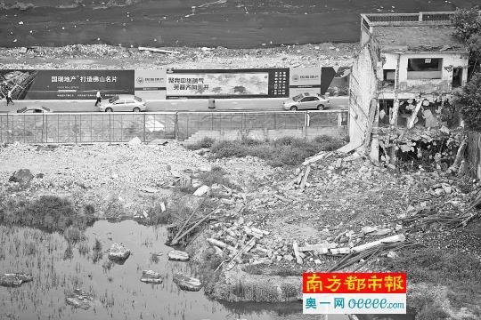 """5月9日,汾宁路西段一栋塌了一半的老屋子。阁下围墙上地产商打出""""打造佛山咭片""""标语。南都记者 张明术 摄"""