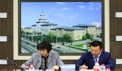 上图:国双科技联席总裁李峰(右)代表公司与哈工大签署捐赠协议
