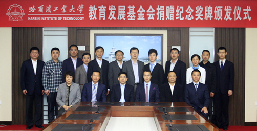 上图:国双科技董事长兼CEO祁国晟(右)从哈工大党委书记王树权(左)手中领取捐赠纪念奖牌和杰出教育贡献奖牌。