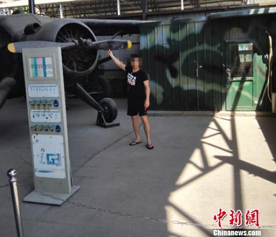 图为5月16日的北京军事博物馆广场内展区,一位旅客跨过围栏手摸展品照相