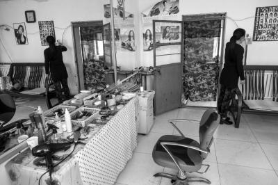 李红在本人开的剃头店内看日历,平常主顾并未几。京华时报记者蒲东峰摄