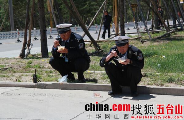 右一:忻州市交警支队支队长袁小波 左一:五台山交警大队大队长申保华   一线检查中在路边吃着过时午餐