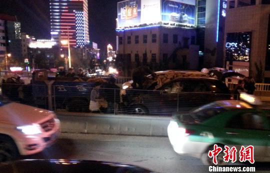 图为关联职员正在清算沉积在追飞驰车顶部的砖块。 胡贵龙 摄