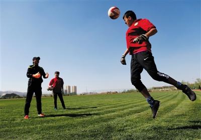 队中的守门员在守门员教练的指导下进行训练。