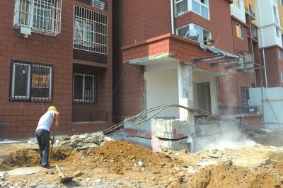 工人正在楼体旁进行施工。京华时报记者谭青摄