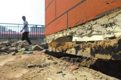 楼体底部与地面之间的裂缝。京华时报记者谭青摄