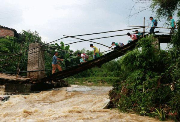 5月25日消息,广西梧州,龙圩区广平镇看到一座被洪水冲毁的桥梁,由于缺少安全围闭设施,不少居民及小学生上下学都会通过这座断桥,桥下是水流湍急的河水,让人不禁为他们的安全捏了一把汗。图片来源:CFP/江西都市报