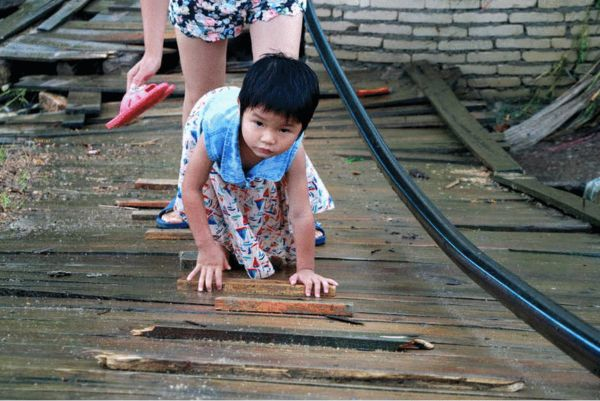 """图为5月25日,广西梧州,一位小女孩手脚并用地""""爬""""过单薄的木板便桥,她母亲在后面为她撑伞。"""