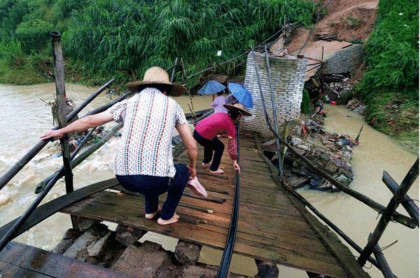"""图为5月25日,广西梧州,几名妇女手脚并用地""""爬""""过单薄的木板便桥。"""