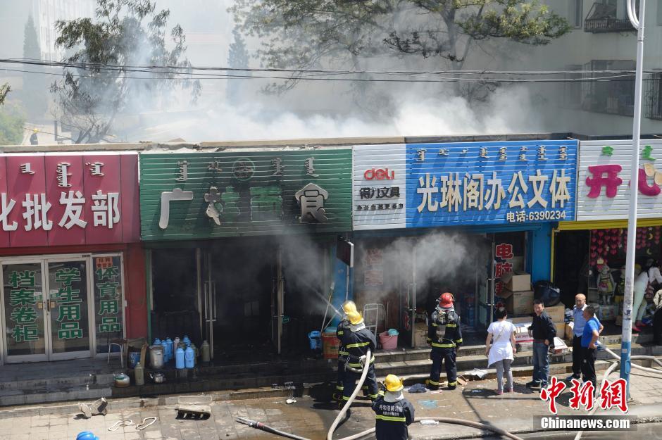 5月26日,呼和浩特市市区内一经营面食的饭店发生火灾,火势殃及周围店铺与饭店后墙紧靠着的车棚。现场部分市民听到有爆炸声,疑为煤气引起的火灾,暂无人员伤亡报告。图为消防战士现场实施灭火。刘文华