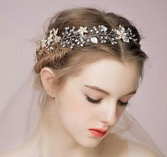 别致的盘发,细细地盘在脑后,整体没有拘紧反而更为自然,扎上浪漫的花式发饰后,端庄大气又彰显出新娘的娇俏。   复古宫廷新娘发型图片02: